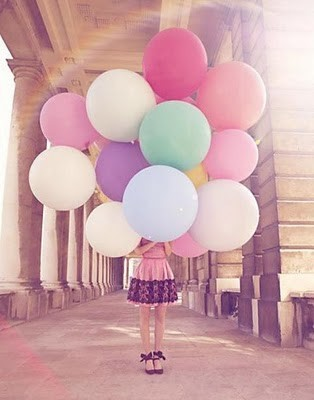 girl holding balloons, her face obscured